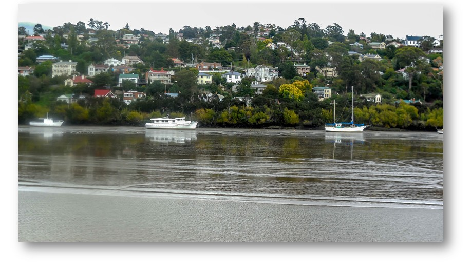Boats across the river sitting high on the mud flats with the river running down the middle.